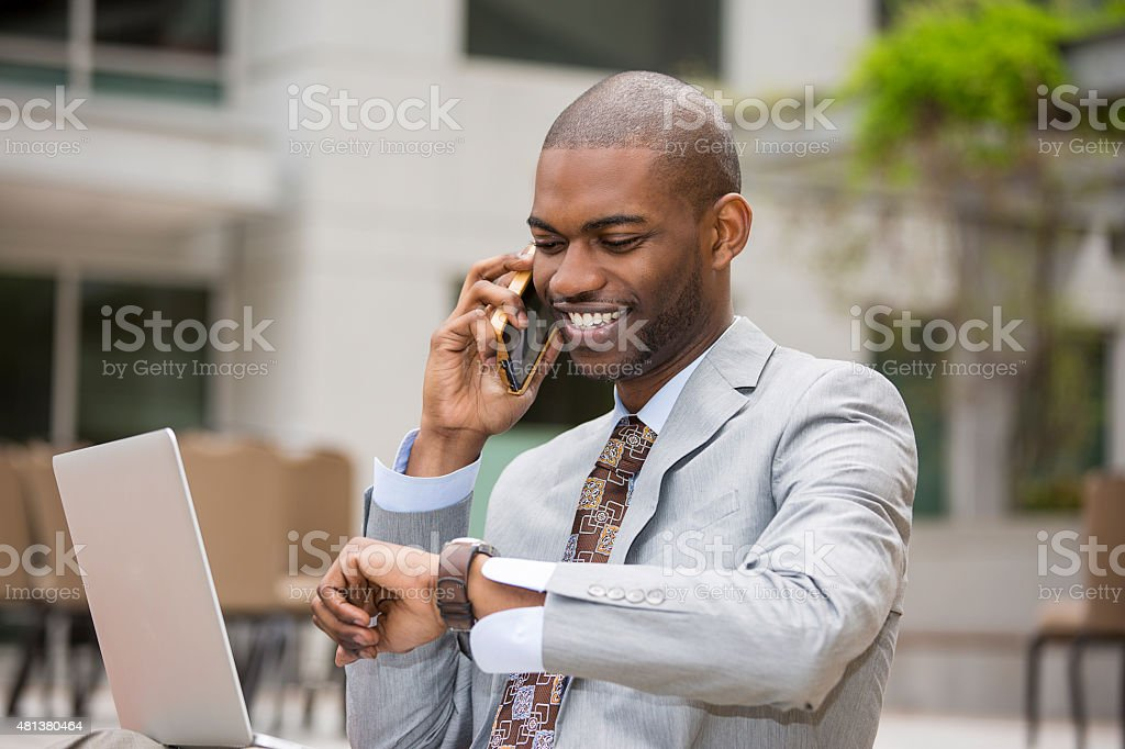 businessman working with laptop talking on mobile phone stock photo