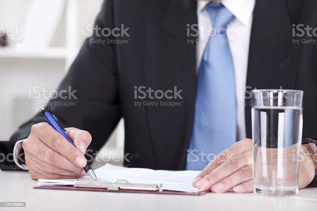 Businessman writes with  pen on paperwork royalty-free stock photo