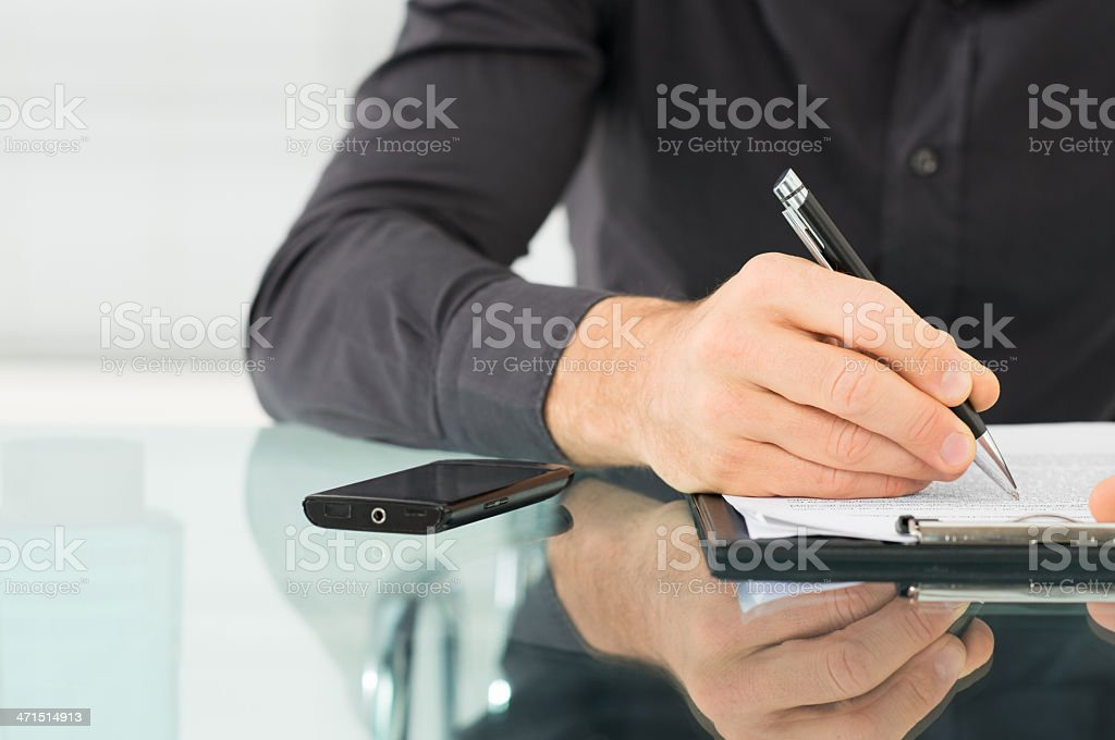 Businessman Writing a Paperwork stock photo