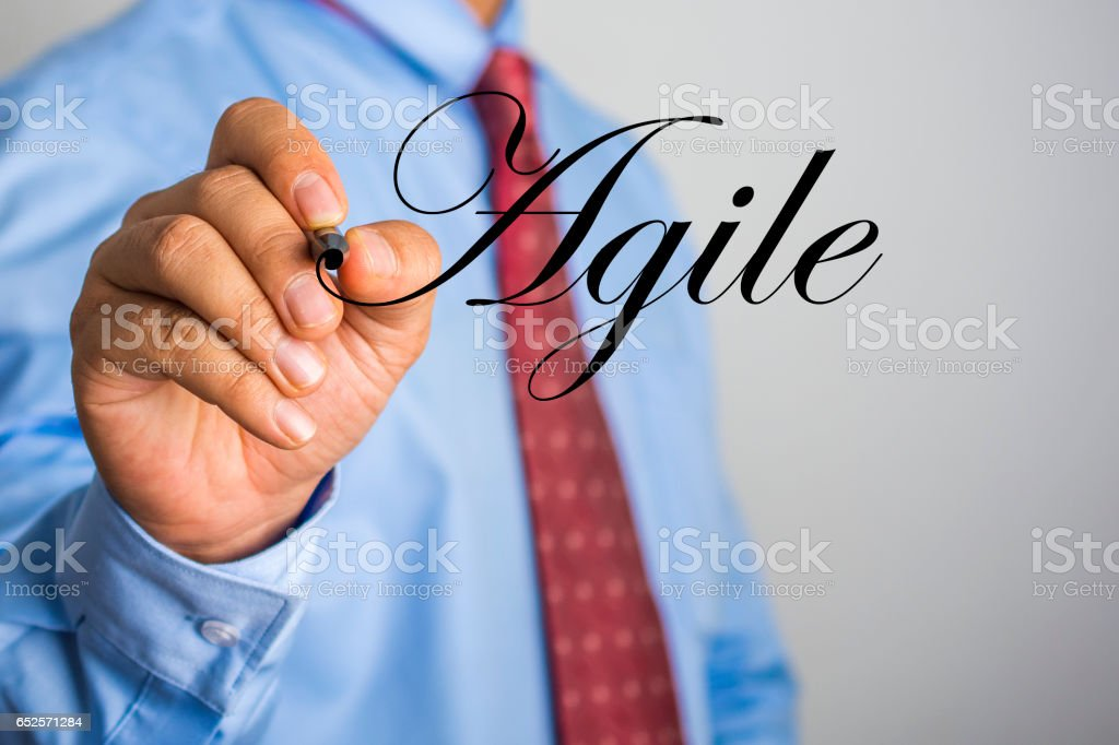 Businessman writing Agile word on virtual screen. stock photo
