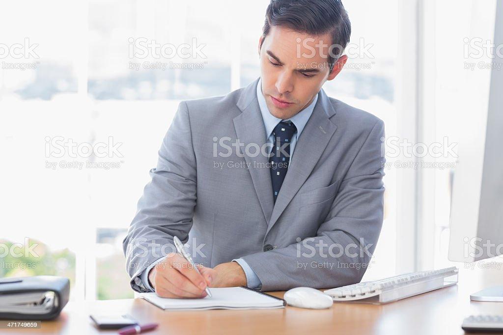 Businessman writing at his desk royalty-free stock photo