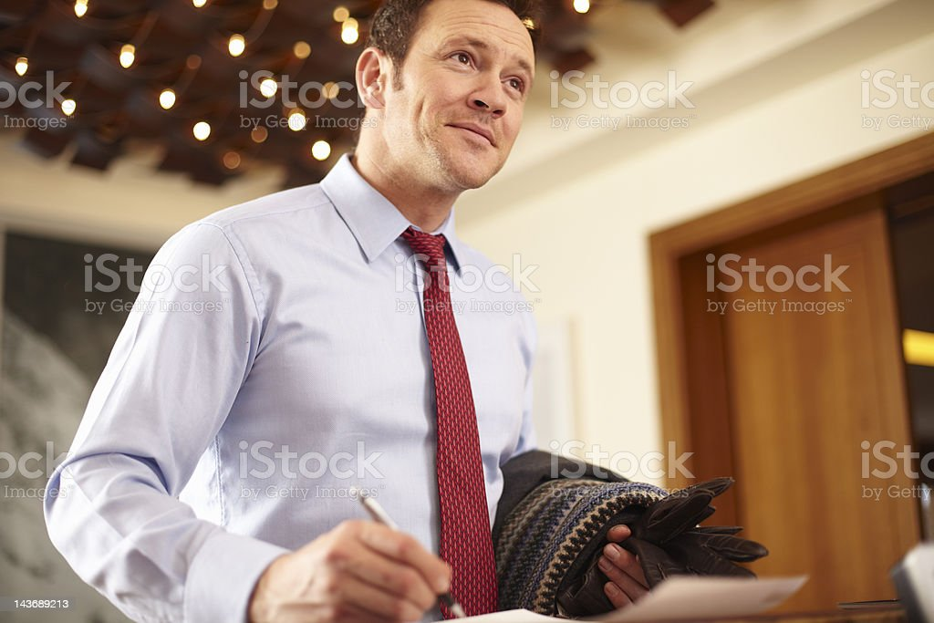 Businessman writing at hotel front desk royalty-free stock photo