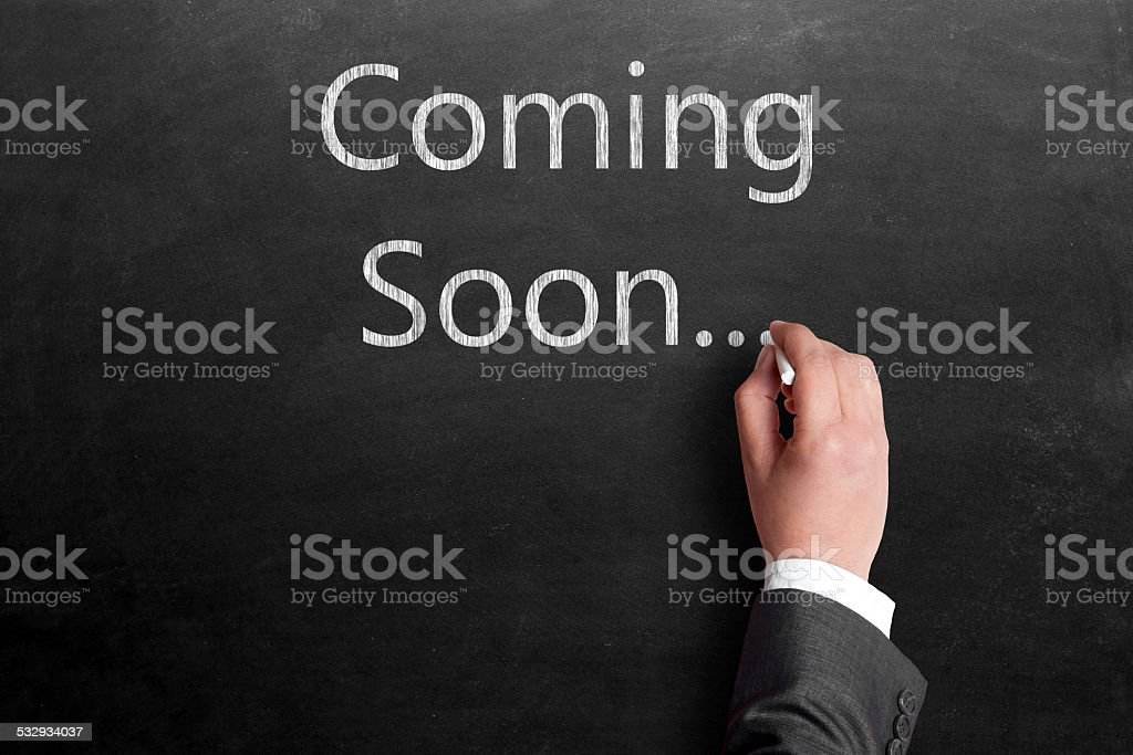 Businessman writing coming soon sign on blackboard stock photo