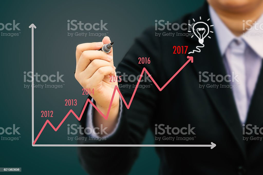 Businessman writing Estimate graph for year 2017 (Pastel tone). stock photo