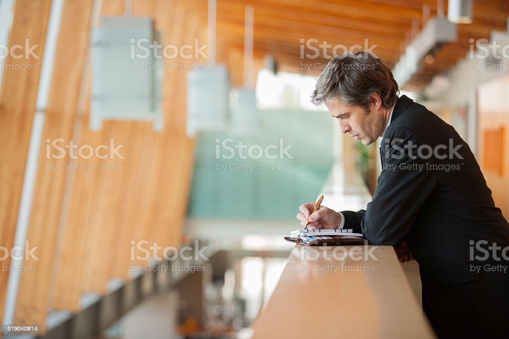 Businessman writing in a weekly planner stock photo