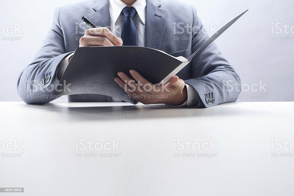 Businessman Writing in Folder stock photo