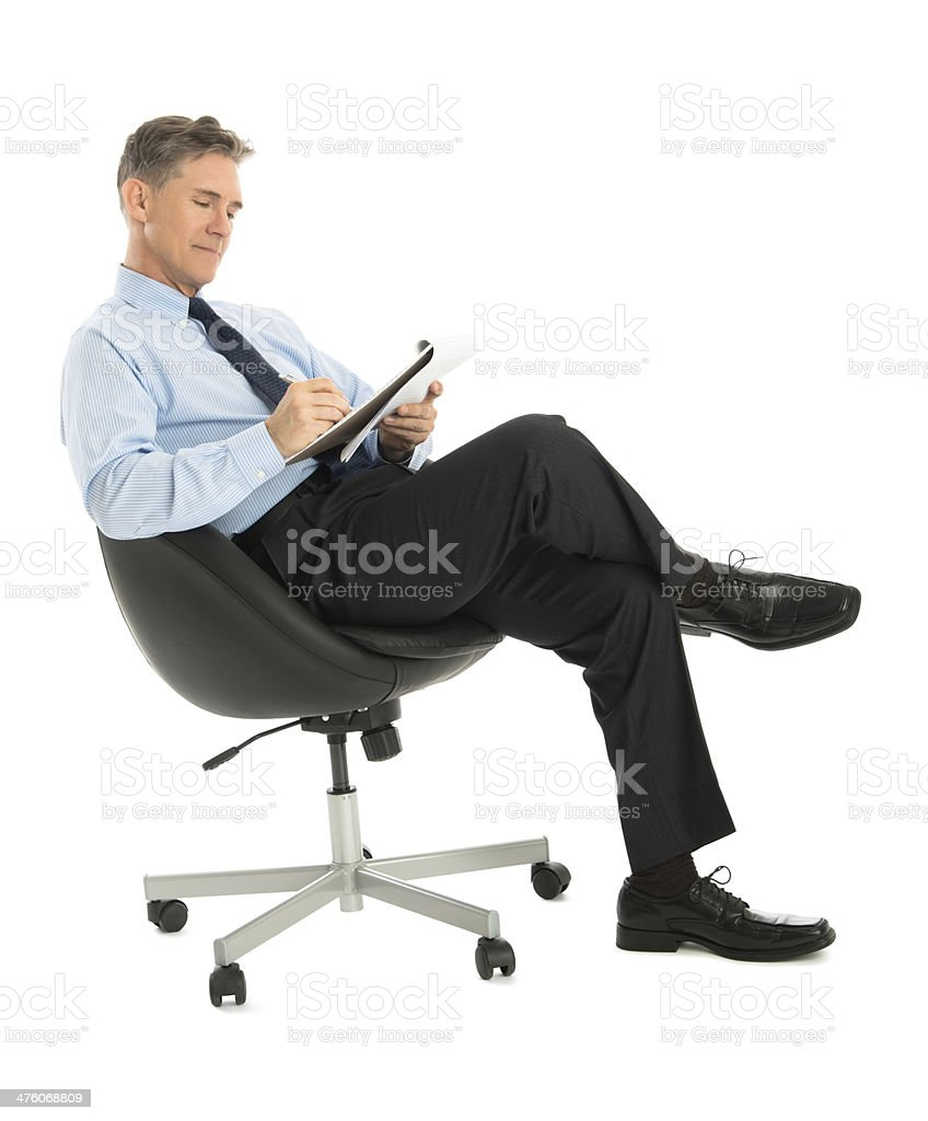 Businessman Writing In Note Pad While Sitting On Office Chair stock photo