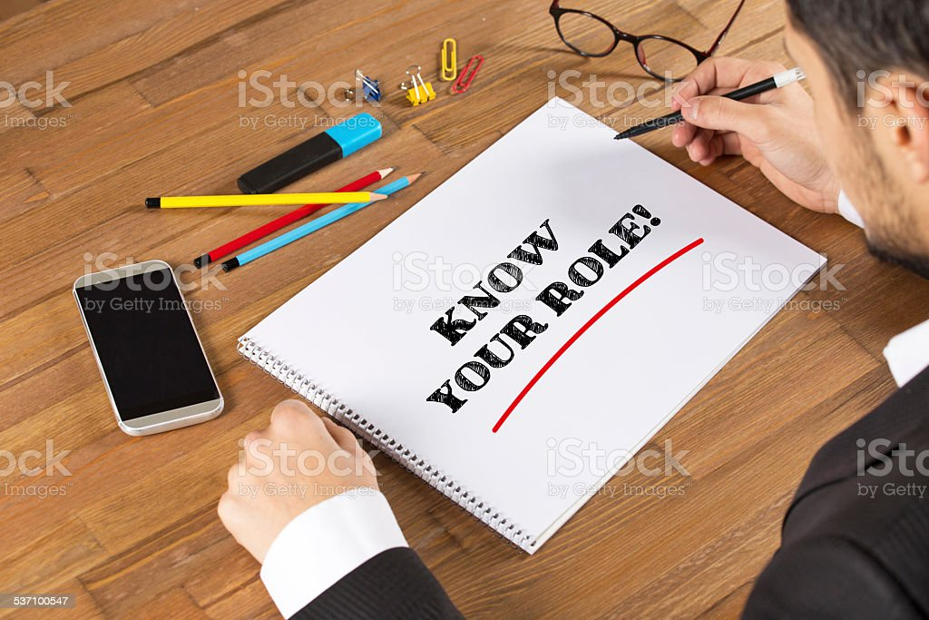 Businessman writing Know Your Role! on a notepad stock photo