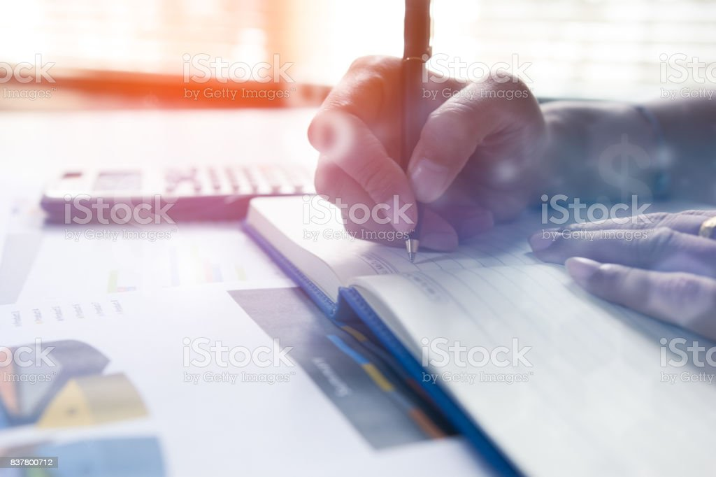Businessman writing on notebook on wooden table, People are recording accounting data calculated from a calculator.Concept finance planing and analyzes management. stock photo