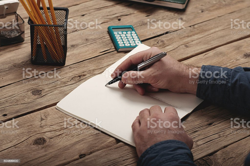 businessman writing to notebook on a wooden table stock photo
