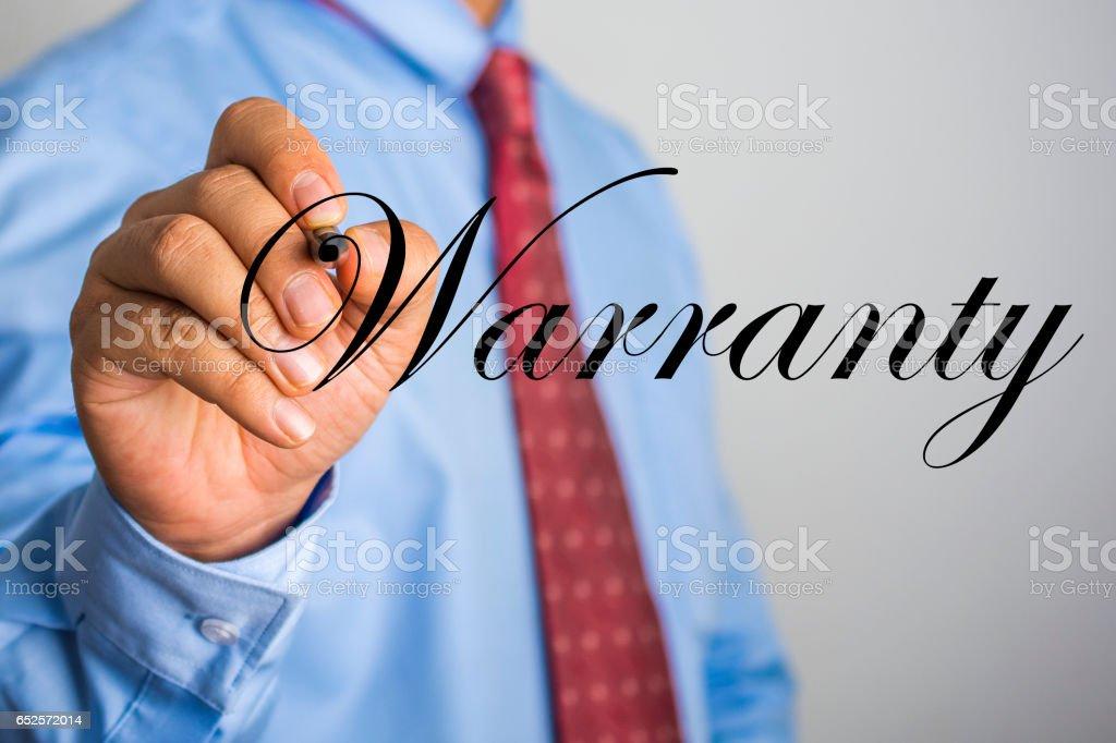 Businessman writing Warranty word on virtual screen. stock photo
