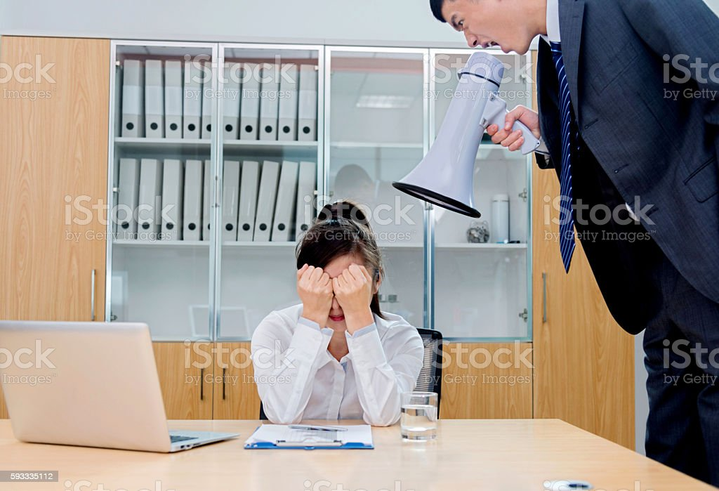 Businessman yelling at colleague through a bullhorn stock photo