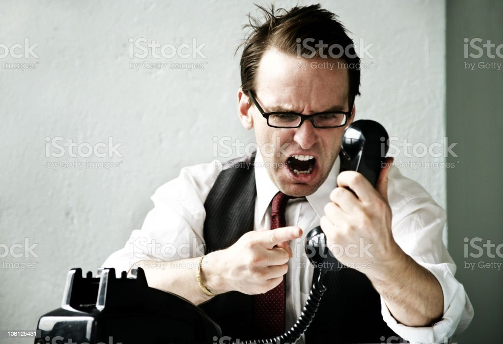 Businessman yelling on phone (close-up) royalty-free stock photo
