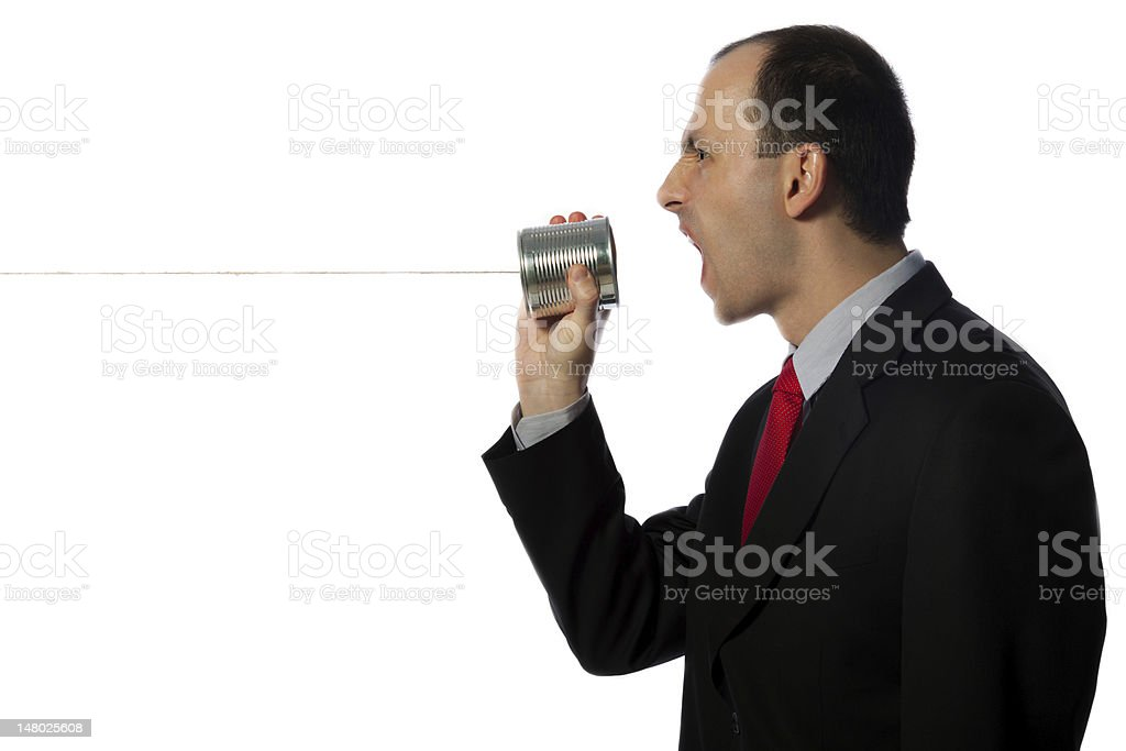 Businessman yelling through an oldschool can phone, horizontal, close up stock photo