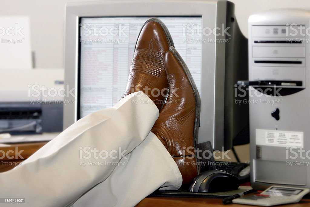 Businessman's Feet Propped Up On The Desk royalty-free stock photo