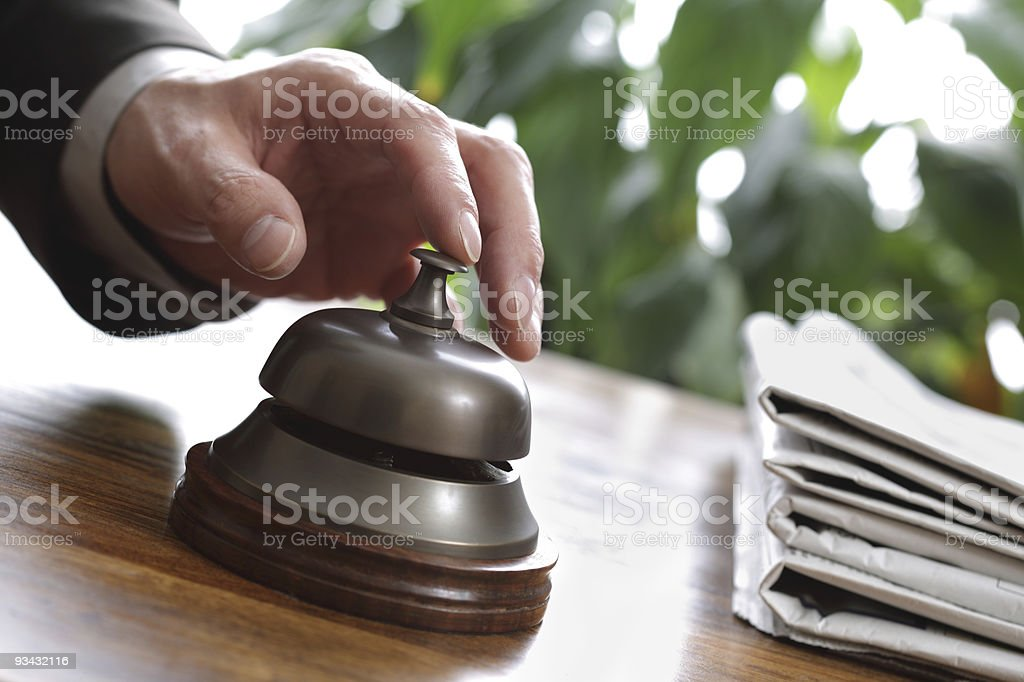 Businessman's finger about to ring hotel service bell royalty-free stock photo