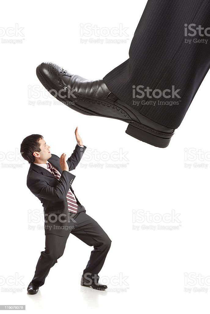 Businessman's foot stepping on tiny businessman royalty-free stock photo
