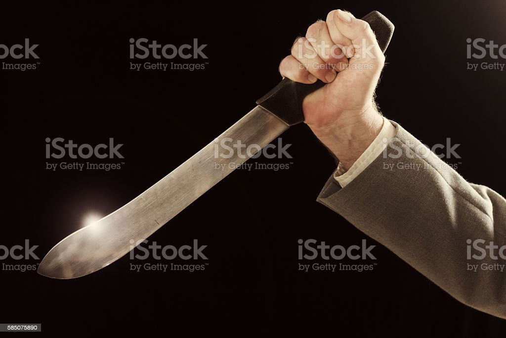 Businessman's hand holds knife, ready to stab stock photo