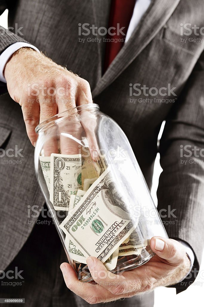 Businessman's hand in money jar. White-collar crime or personal stash? royalty-free stock photo