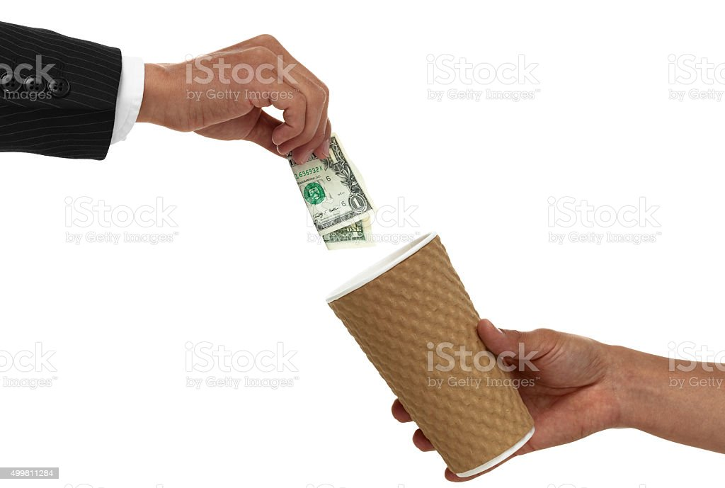 Businessmans hand putting change into cup being held out stock photo