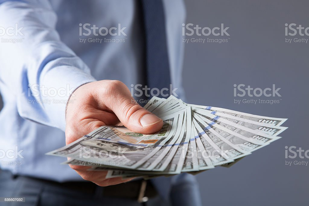 Businessman's hand reaching out dollars stock photo