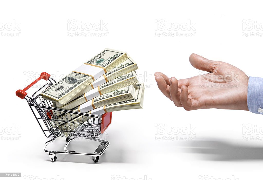 businessman's hand & shopping cart full of american dollar banknotes stock photo