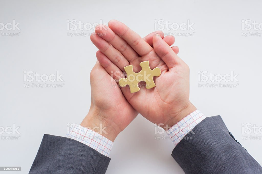 Businessman's hand with a puzzle stock photo