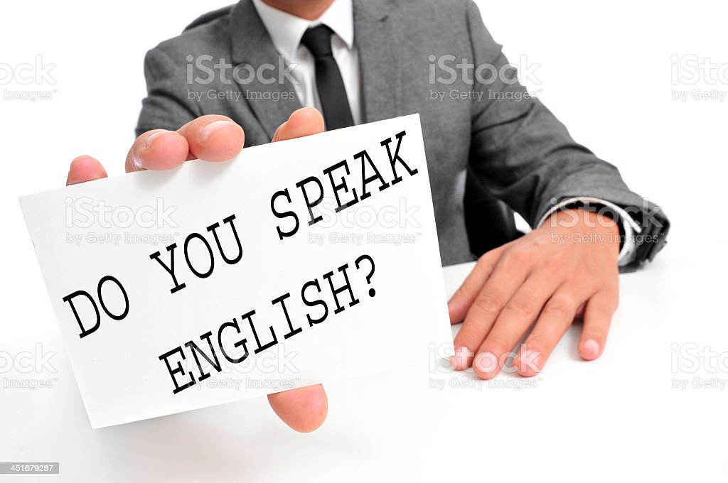 Businessman's hand with sign that says DO YOU SPEAK ENGLISH stock photo