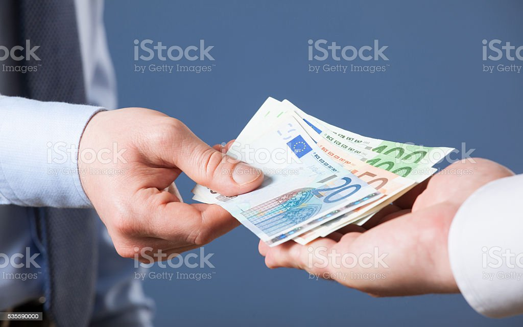 Businessman's  hands exchanging euro on blue background stock photo