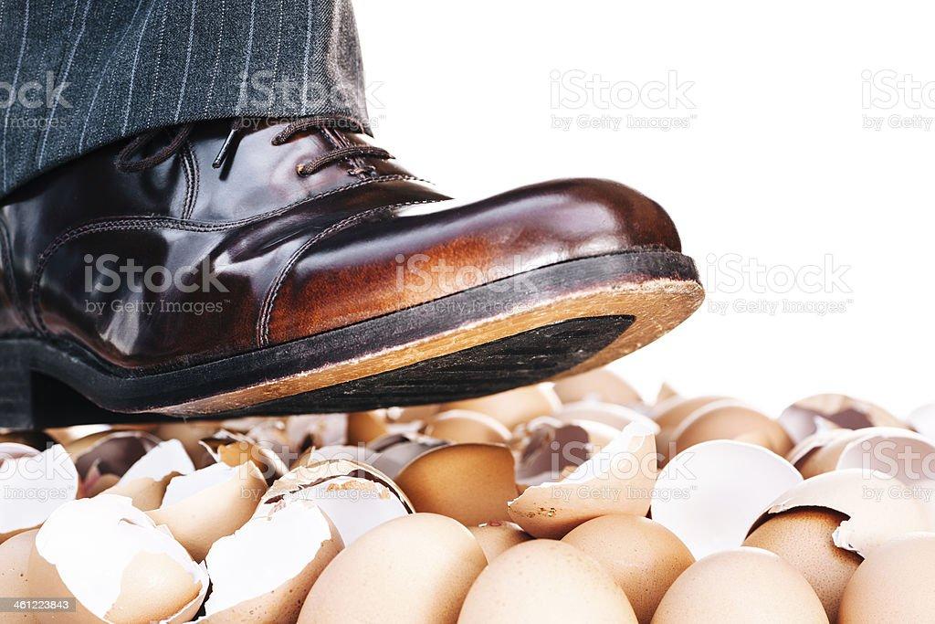 Businessman's shoes walking on eggshells stock photo