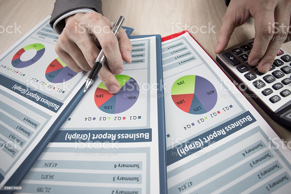 businessmen analysing a bar graph using a manual calculator stock photo
