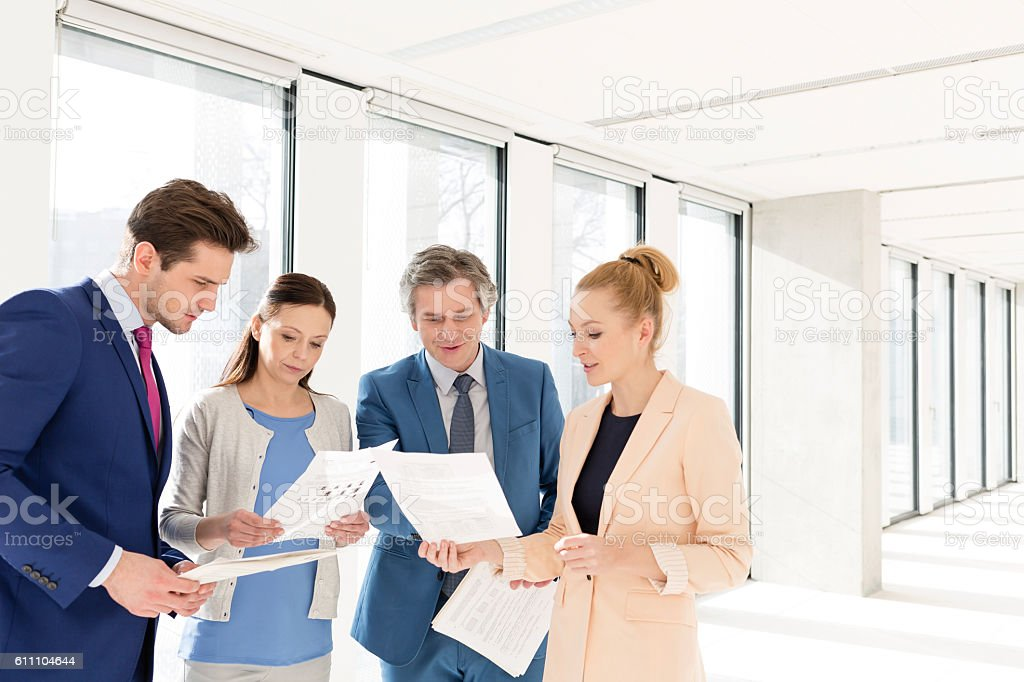 Businessmen and businesswomen discussing over documents in new office stock photo
