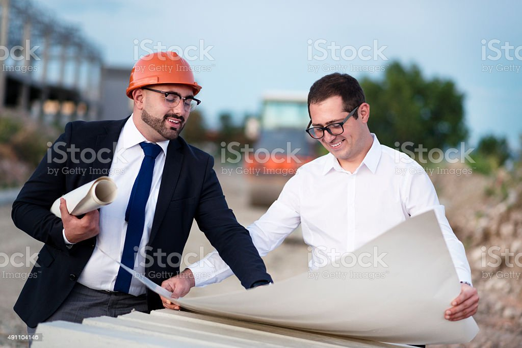 Businessmen and Construction Worker Checking Blueprints stock photo
