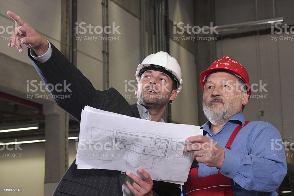 businessmen and older worker over blueprints royalty-free stock photo