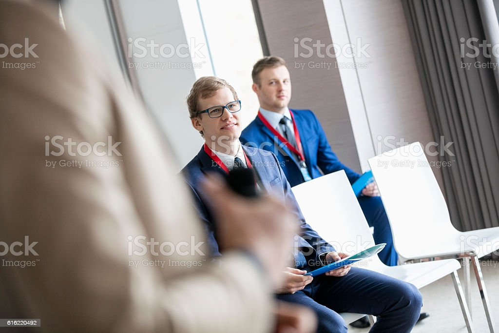 Businessmen and public speaker in seminar hall stock photo