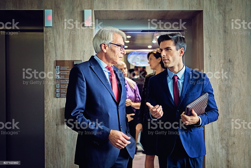 Businessmen are exiting from the elevator in the company building stock photo