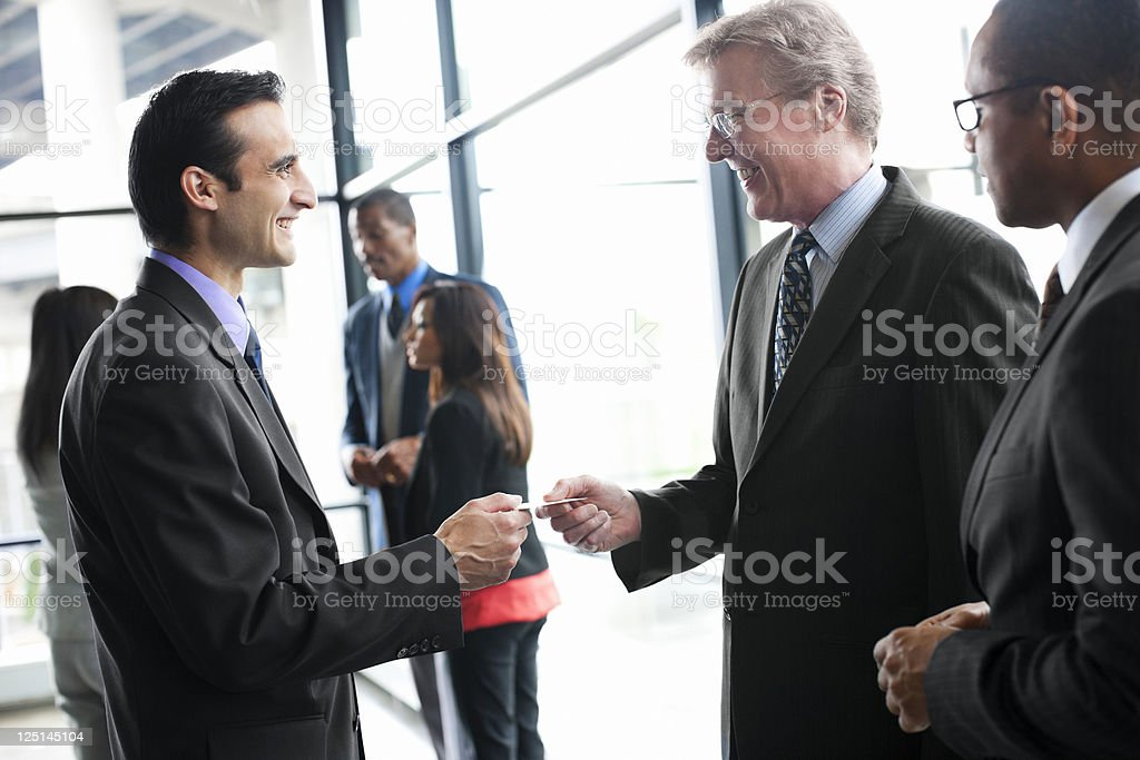 Businessmen at Networking Event Exchanging Business Cards stock photo
