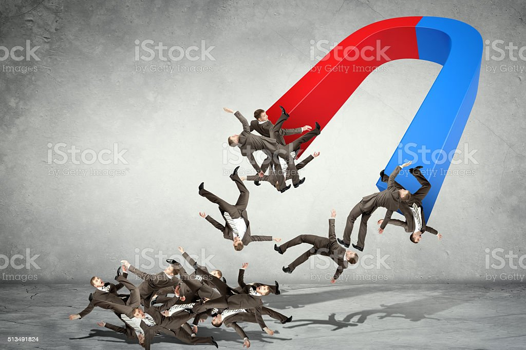 Businessmen attracted within magnet stock photo