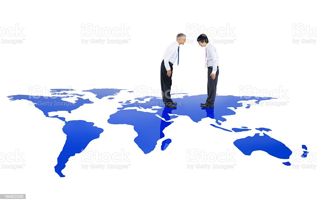 Businessmen bowing on world map royalty-free stock photo