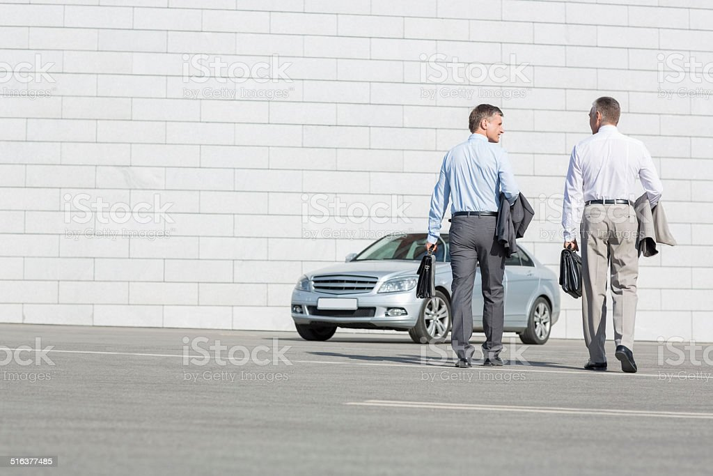 businessmen carrying briefcases while walking towards car on street stock photo