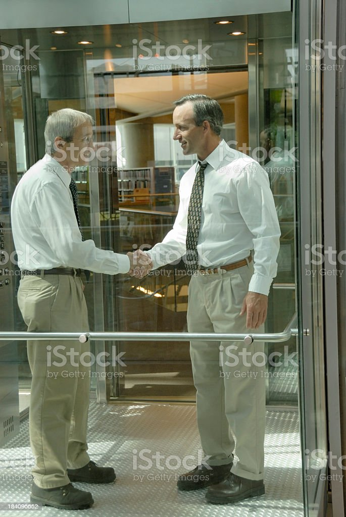Businessmen Concluding Business In A Glass Elevator royalty-free stock photo