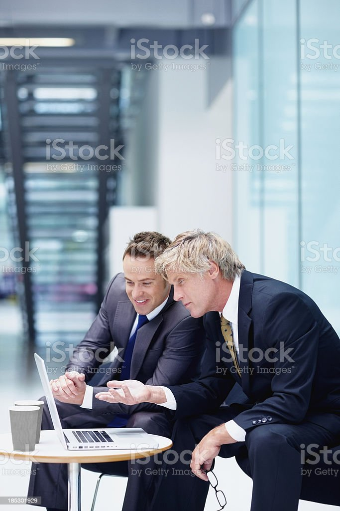 Businessmen conversing while looking at a laptop royalty-free stock photo
