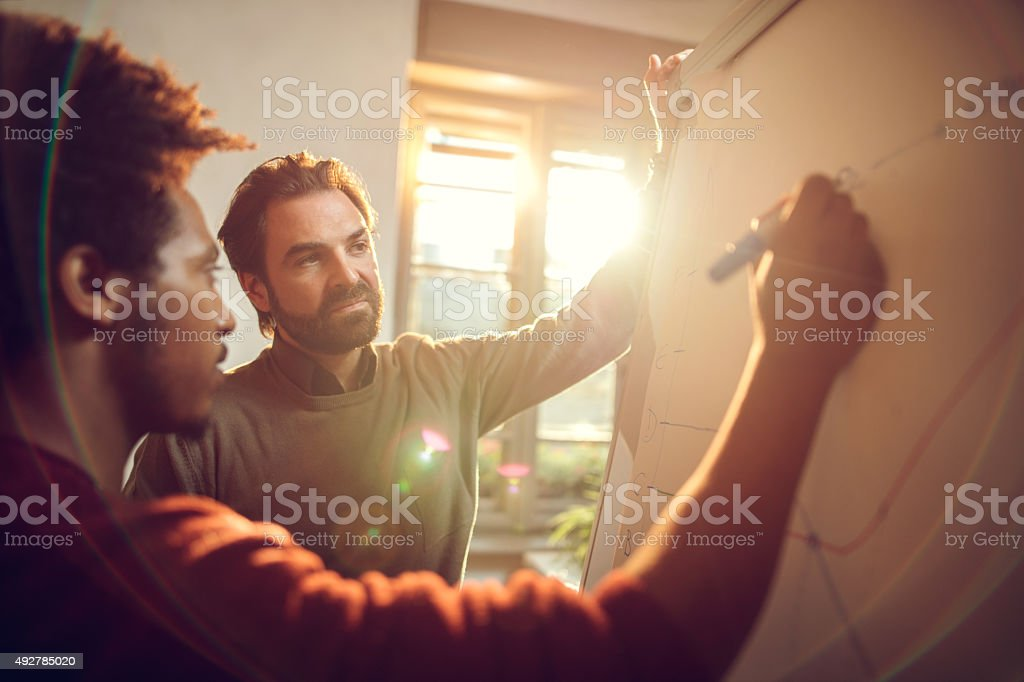 Businessmen cooperating while drawing a business chart at office stock photo