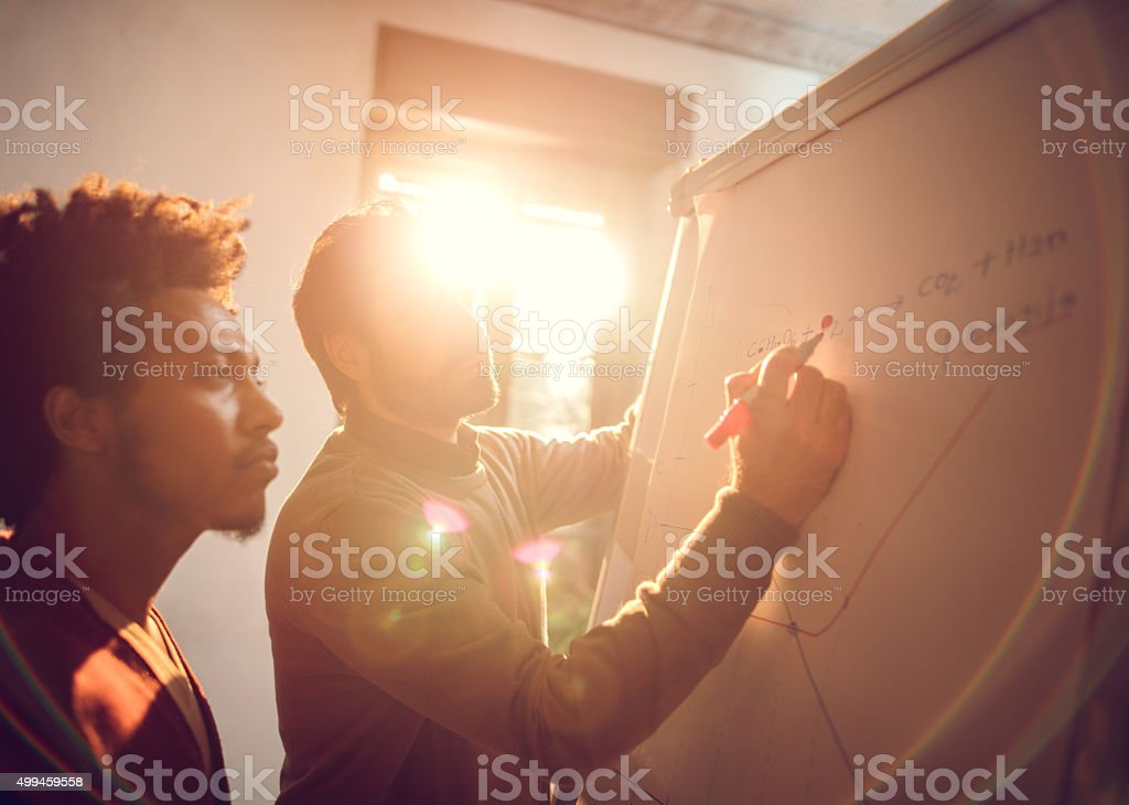Businessmen cooperating while drawing a business chart at office. stock photo