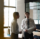 Businessmen discussing in brightly lit office