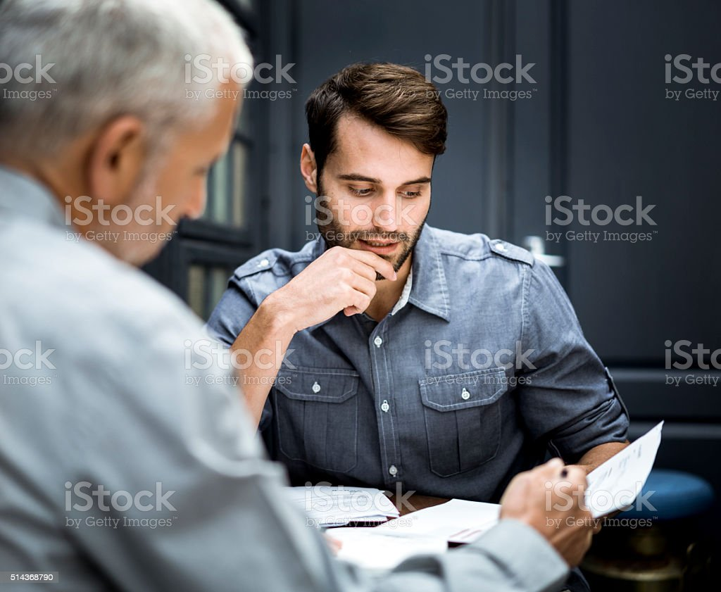 Businessmen discussing over documents in office stock photo