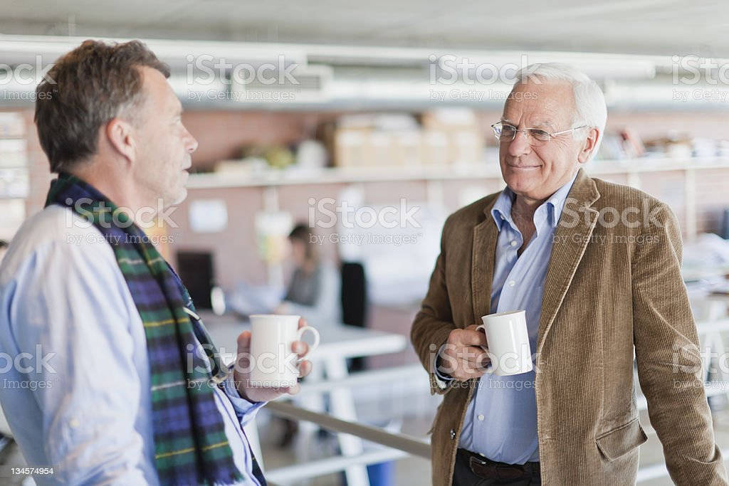 Businessmen drinking coffee together stock photo