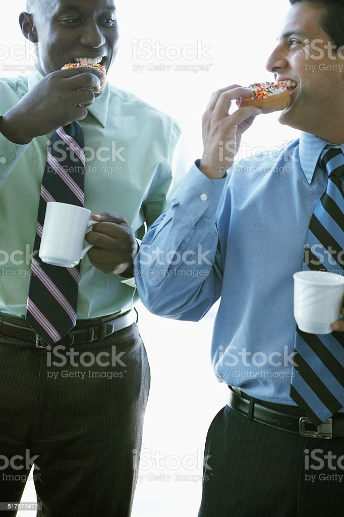 Businessmen eating donuts stock photo