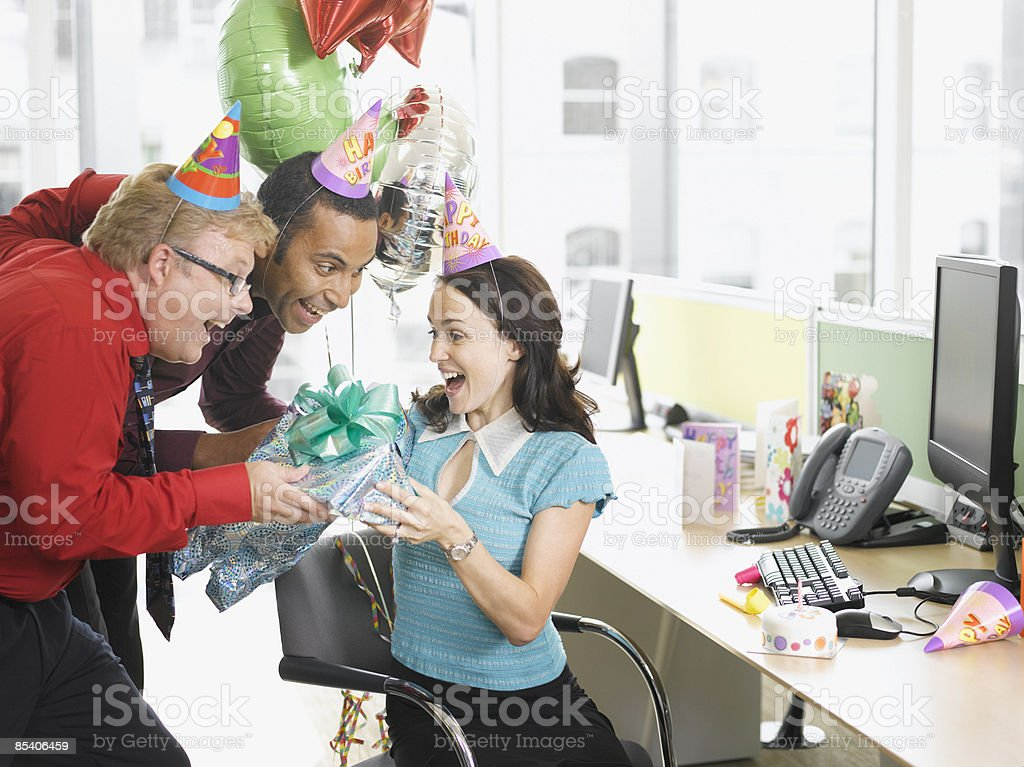 Businessmen giving birthday gift to co-worker royalty-free stock photo