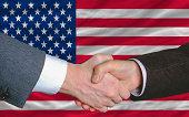 businessmen handshake after good deal in front of america flag